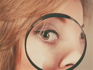 photo of girl looking through magnifying glass