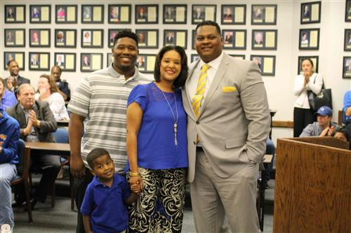 new athletic director with family in a photo